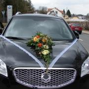 Schwarzes Auto mit Blumenschmuck auf der Motorhaube